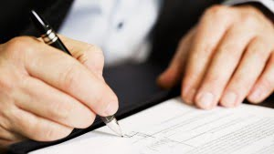 How to Form an LLC in California Businessman sitting at office desk signing a contract with shallow focus on signature.