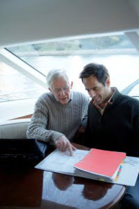 Senior and mature man sitting on yacht looking at file together Reno Corporate Services Attorneys
