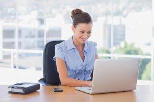 Happy businesswoman on her laptop